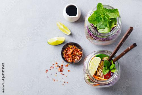 Fotografie, Obraz  Noodles soba salad, soup with vegetables, tofu and chicken in jars