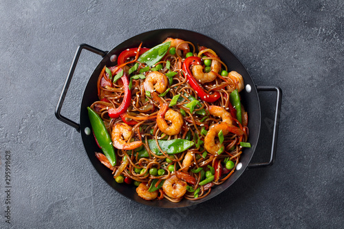 Photo Stir fry noodles with vegetables and shrimps in black pan