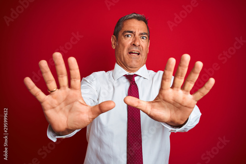 Fotomural Handsome middle age businessman standing over isolated red background afraid and terrified with fear expression stop gesture with hands, shouting in shock