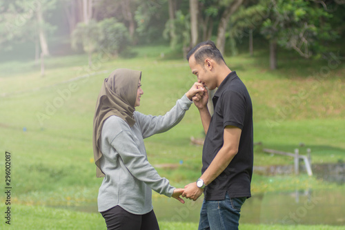 Fototapeta  Asian young Muslim couples are enjoying being together by dancing in the open gr