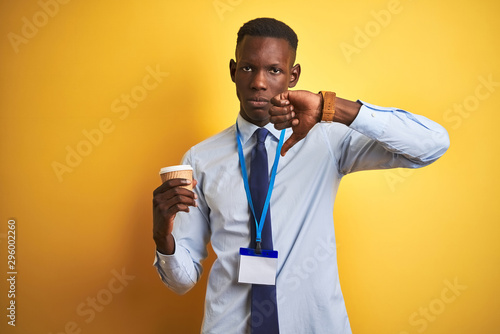 African american businessman wearing id drinking coffee over isolated yellow bac Tablou Canvas