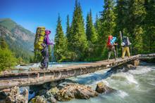 Hikers Crossing Over Wood Brid...