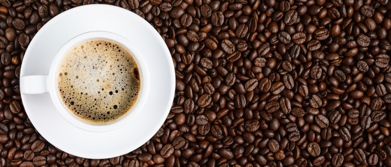 panoramic coffee background of a cup of black coffee covered with coffee bubb...
