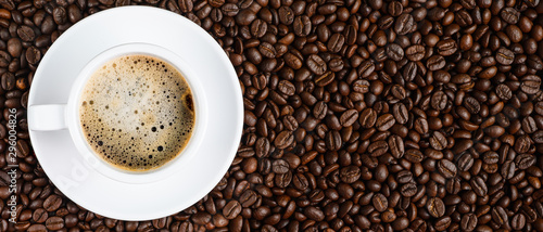 Photo sur Toile Café en grains panoramic coffee background of a cup of black coffee covered with coffee bubble on roasted arabica coffee beans