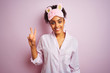 Young african american woman wearing pajama and mask over isolated pink background showing and pointing up with fingers number two while smiling confident and happy.