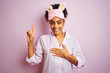 Young african american woman wearing pajama and mask over isolated pink background smiling swearing with hand on chest and fingers up, making a loyalty promise oath