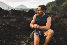 Young Hipster Runner With Beard Using Smart Watch And Listening Music In Wireless Headphones Before Running Outdoors.