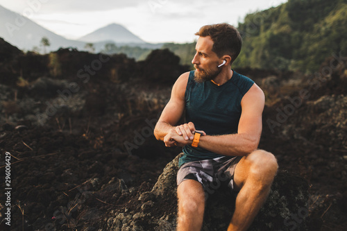 Fotografía  Young hipster runner with beard using smart watch and listening music in wireless headphones before running outdoors