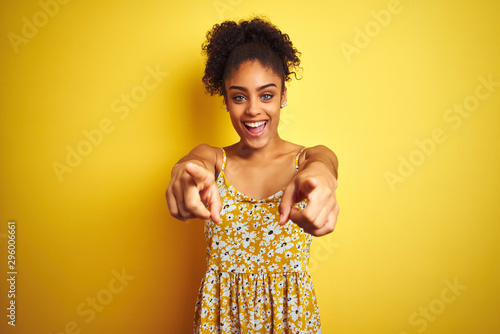 Fotografie, Obraz African american woman wearing casual floral dress standing over isolated yellow
