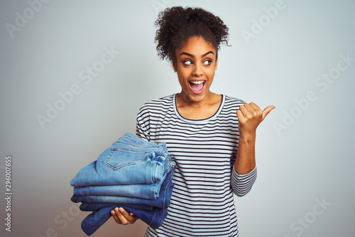 Valokuva  Young african american woman holding stack of jeans over isolated white backgrou