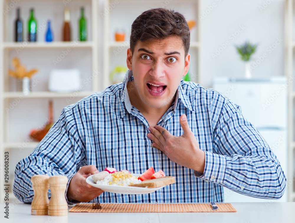 Fototapety, obrazy: Young husband eating tasteless food at home for lunch