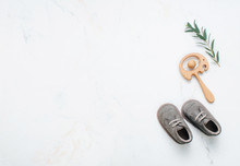 Newborn Baby Shoes And Wooden Beanbag On Marble Background