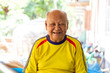 Leinwandbild Motiv Portrait of elderly asian man  is sitting smiling with yellow shirt at Sisaket province , Thailand.