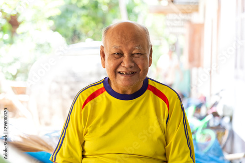Portrait of elderly asian man  is sitting smiling with yellow shirt at Sisaket province , Thailand Fototapete