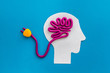 Brain charging and mental rest. Plug and cable leads to plastiline meanders on blue background top view