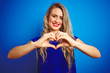 Young beautiful woman standing over blue isolated background smiling in love showing heart symbol and shape with hands. Romantic concept.
