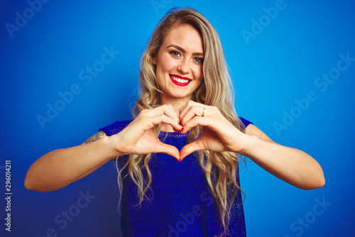 Fototapeta Young beautiful woman standing over blue isolated background smiling in love showing heart symbol and shape with hands. Romantic concept. obraz