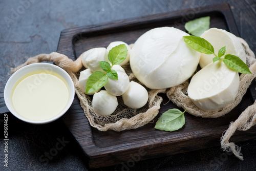 Cuadros en Lienzo Mozzarella cheese with olive oil and green basil leaves on a black wooden servin