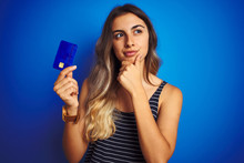 Young Beautiful Woman Holding Credit Card Over Blue Isolated Background Serious Face Thinking About Question, Very Confused Idea