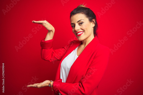 Fototapeta Young beautiful business woman standing over red isolated background gesturing with hands showing big and large size sign, measure symbol. Smiling looking at the camera. Measuring concept. obraz
