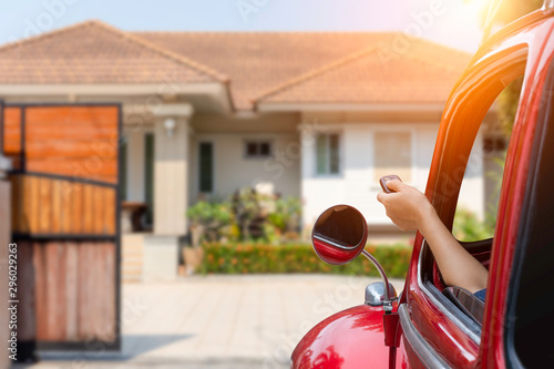 Stampa su Tela Woman in car, hand opening the automatic gate by using remote control