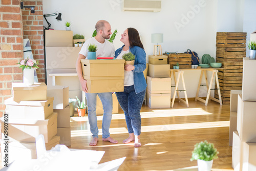 Young couple moving to a new home, smiling happy holding cardboard boxes Fototapet