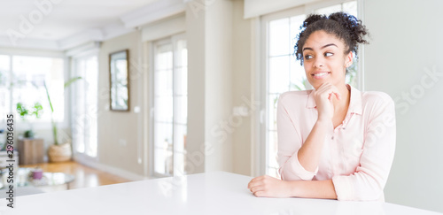Wide angle of beautiful african american woman with afro hair with hand on chin thinking about question, pensive expression Wallpaper Mural