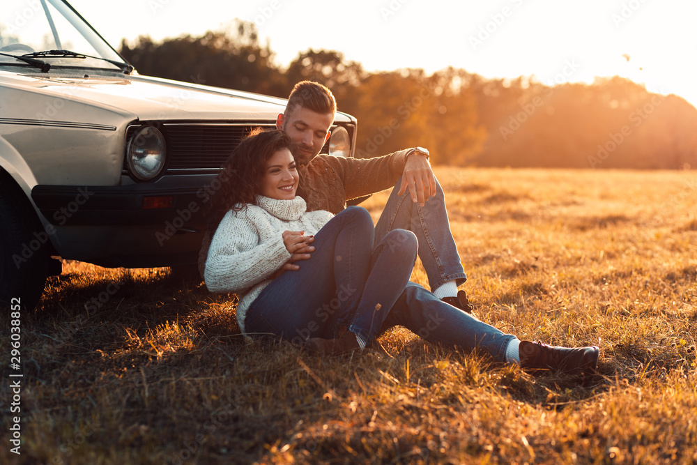 Fototapety, obrazy: Beautiful young couple enjoying time together outdoor sitting on meadow leaning on old fashioned car embracing each other.