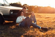 Beautiful Young Couple Enjoying Time Together Outdoor Sitting On Meadow Leaning On Old Fashioned Car Embracing Each Other.