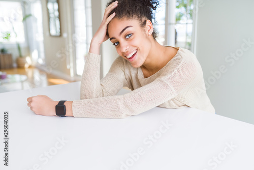 Fotomural  Beautiful young african american woman smiling cheerful leaning on the table com
