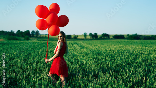 Young beautiful woman in red dress posing in green field with red balloons Wallpaper Mural
