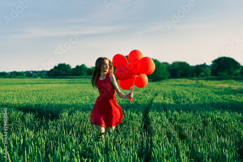 Freedom happy woman running with red balloons on green summer field Wallpaper Mural