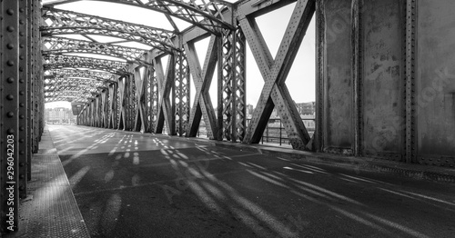 Spoed Fotobehang Bruggen Black and white asphalt road under the steel construction of a bridge in the city on a sunny day. Evening urban scene with the sunbeam in the tunnel. City life, transport and traffic concept.
