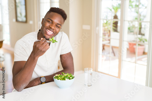 Handsome african young man eating a healthy vegetable salad using a fork to eat Canvas Print