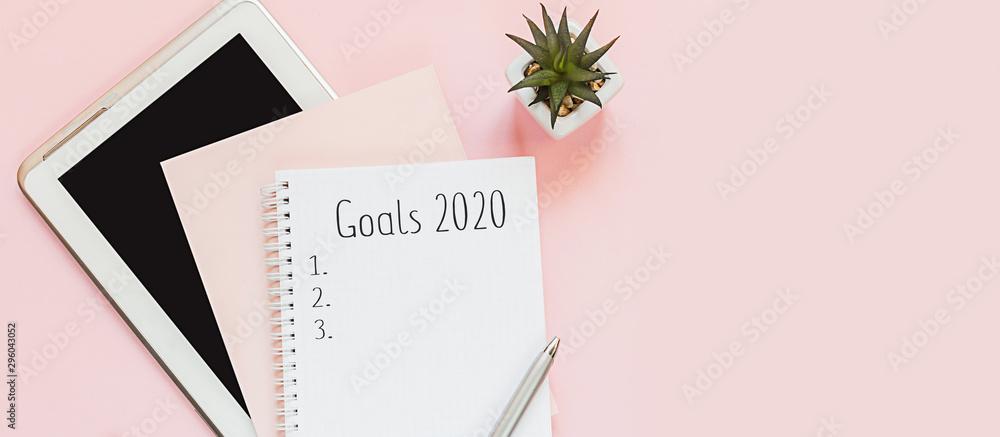 Widok z góry płaskiego pulpitu i notesów do zapisywania celów i planów. Cel noworoczny 2020, plan, tekst akcji na notatniku z akcesoriami biurowymi. Motywacja biznesowa, koncepcja inspiracji.