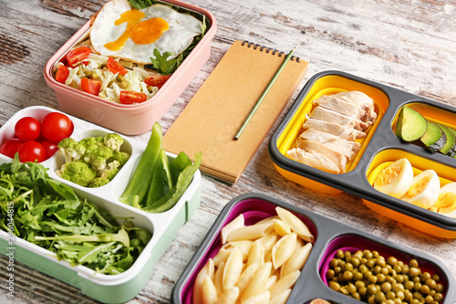 Notebook with healthy food in lunch boxes on white wooden background. Diet concept - 296044815