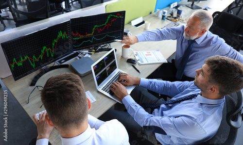 Fotografía  Group of modern business men in formalwear analyzing stock market data while working in the office