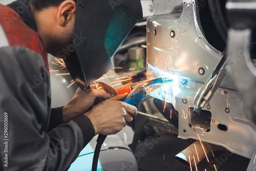 Industrial worker at car service welds automotive body. Metalworking with carbon dioxide welding. - 296050669