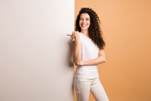 Photo Of Amazing Lady Indicating Finger On Empty Discount Banner Standing Near Big White Placard Wear White Casual Clothes Isolated Beige Pastel Color Background