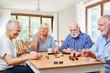 Leinwandbild Motiv Group of seniors playing dominoes