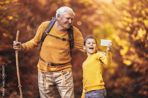 Fotografía  Grandfather and grandson hiking together in autumn park, make selfie photo