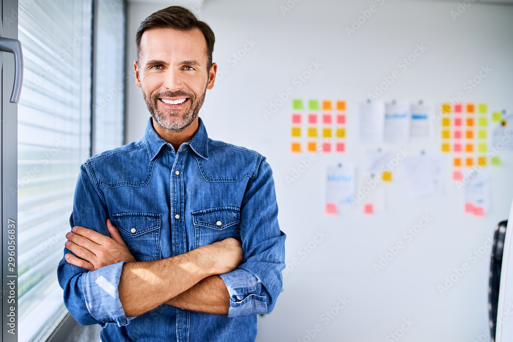 Fototapeta Portrait of handsome creative businessman looking at camera with arms crossed in office
