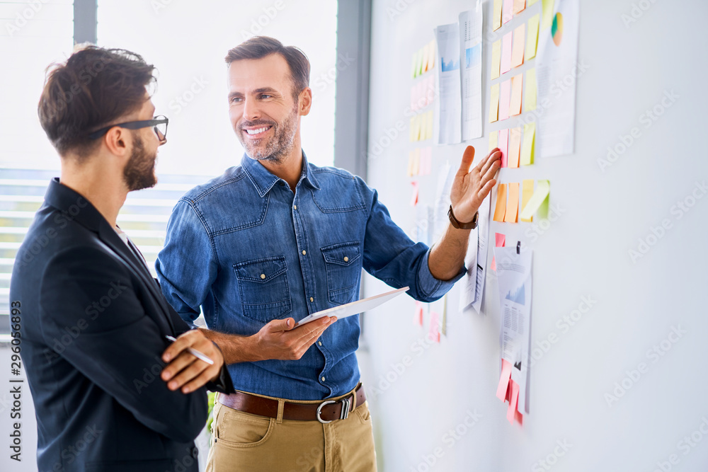 Fototapeta Creative worker and businessman smiling and talking in modern office