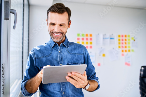 Fototapety, obrazy: Handsome startup businessman looking at tablet in office
