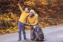 Senior Man Reading Map On Digital Tablet With Grandson In Forest Walk.