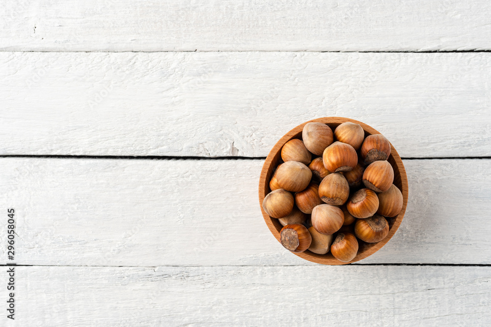 Fototapety, obrazy: Overhead shot of hazelnuts in bowl on white wooden table. Healthy snacks