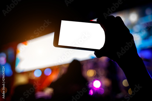 Smartphone in hands during music show. - 296069224