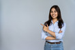 Confident smiling indian young woman professional student customer saleswoman looking at camera pointing at sales copy space isolated on grey studio background, happy lady showing aside portrait