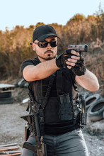 Portrait Of A Heavily Armed Young Man Shooting A Gun Outdoors.Special Forces Soldier On A Practice.