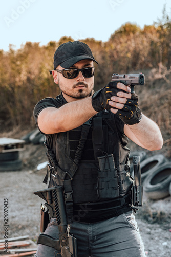 Tela Portrait of a heavily armed young man shooting a gun outdoors